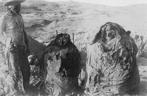 Historic Image of two mummy bundles and a workman from Max Uhle's excavation at Pachacamac, Peru. Penn Museum Image 140697.