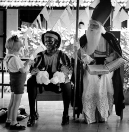 Sinterklaas and Black Peter with a child, via Wikimedia